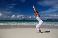 Caucasian woman practicing yoga at seashore of tropic ocean Royalty Free Stock Photos