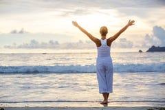 Caucasian woman practicing yoga at seashore of tropic ocean Royalty Free Stock Photography