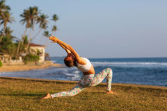 Caucasian woman practicing yoga at seashore of tropic ocean Royalty Free Stock Photos