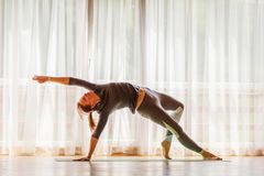 Caucasian woman is practicing yoga at studio.  stock images