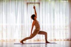 Caucasian woman is practicing yoga at studio.  stock photos