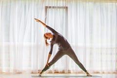 Caucasian woman is practicing yoga at studio.  royalty free stock image