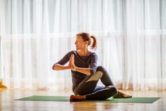 Caucasian woman is practicing yoga at studio.  royalty free stock photography