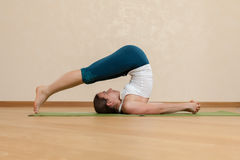 Caucasian woman is practicing yoga at studio Stock Image