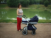 Caucasian woman with a pram on walk in park. Near the pond Stock Photos