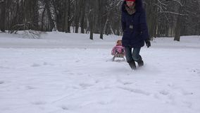 Caucasian woman pulling baby child on sled through snowdrifts. 4K stock video