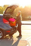 Caucasian woman putting her shopping bags into the car trunk Royalty Free Stock Image