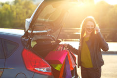 Caucasian woman putting her shopping bags into the car trunk Royalty Free Stock Photography