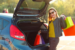 Caucasian woman putting her shopping bags into the car trunk Stock Photography
