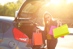 Caucasian woman putting her shopping bags into the car trunk Stock Images