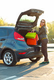 Caucasian woman putting her shopping bags into the car trunk Stock Photo