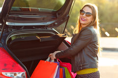 Caucasian woman putting her shopping bags into the car trunk Royalty Free Stock Photo