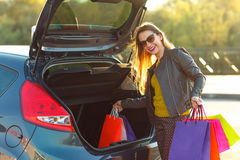 Caucasian woman putting her shopping bags into the car trunk. Smiling Caucasian woman putting her shopping bags into the car trunk- Let's go shopping concept Royalty Free Stock Photos
