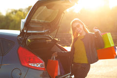 Caucasian woman putting her shopping bags into the car trunk Royalty Free Stock Images