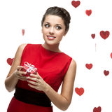 Caucasian woman in red dress holding gift Royalty Free Stock Image