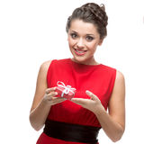 Caucasian woman in red dress holding gift Stock Images