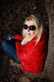 Caucasian woman with red jacket and sunglasses posing on autumn background near tree Stock Photo