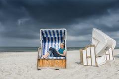 Caucasian woman relaxing in strandkorb at baltic sea stock image