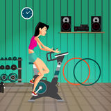 Caucasian woman riding stationary bicycle in the gym. Sporty gir Royalty Free Stock Photo