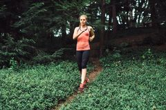 Caucasian woman running on forest trail wearing sport clothes. Stock Images