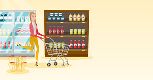 Caucasian woman running with trolley in the store. Young caucasian woman pushing a shopping trolley. Happy woman running with an empty shopping trolley in the Stock Photos