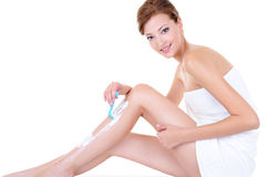 Caucasian woman shaving legs with razor. Beautiful adult caucasian woman shaving legs with razor - isolated royalty free stock photography