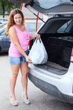 Caucasian woman with shopping bag loading suv Royalty Free Stock Photography