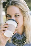 Caucasian Woman Sipping Coffee While Smiling royalty free stock images