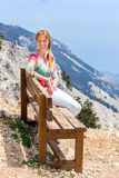 Caucasian woman sitting on bench in mountain landscape. European woman sitting on wooden bench in mountain landscape royalty free stock photos