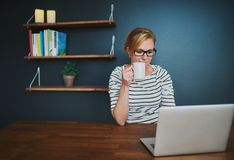 Caucasian woman sitting at desk with laptop stock photography