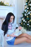 Caucasian woman sitting near Christmass tree and keeping present. royalty free stock photography