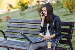 Caucasian woman sitting in park with laptop and eating croissant royalty free stock image