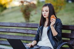 Caucasian woman sitting in park with laptop and eating croissant royalty free stock images