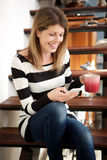 Caucasian woman sitting on stairs and using smart phone at home Stock Photography