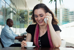 Caucasian woman speaking at phone and drinking coffee in a cafeteria Royalty Free Stock Images