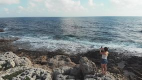 Caucasian woman standing on cliffs with camera cell phone taking photos of sea horizon with strong waves hitting the beach. Waves. Splashing strong wind. Aerial stock video