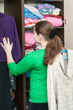 Caucasian woman standing in front of organized closet. At home Royalty Free Stock Image