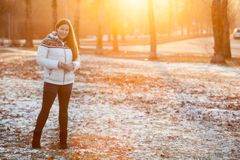 Caucasian woman standing in park in sunlight of sunset sun, copyspace Stock Photography