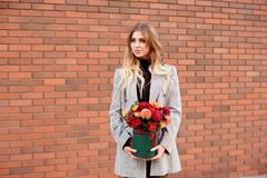 Caucasian woman standing on the street near storefront shop windows holding flower-box with happy smile. stock photos