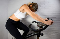 Caucasian Woman on Stationary Bike. Middle aged woman in white tanktop and black leggings doing exercise. Stationary bike with white brick background. Caucasian stock images