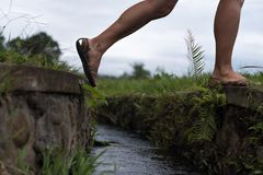 Caucasian woman step over the water ditch. Se has an active vacation in asia and goes for a walk. Caucasian woman step over the water ditch. She has an active stock photos
