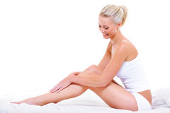 Caucasian woman stroking her beauty legs Stock Photo