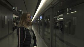 Caucasian woman on subway station waiting train on platform. Traveler young woman in underground. Girl in m moderncity stock video footage
