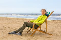 Dutch woman sits in beach chair by the sea royalty free stock photography