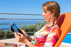 Caucasian woman on sunlounger reading tablet. Middle aged dutch  woman on orange sunlounger reading tablet on terrace Royalty Free Stock Photos