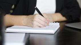 Caucasian woman takes notes in her notebook at the workplace. Close-up plan.