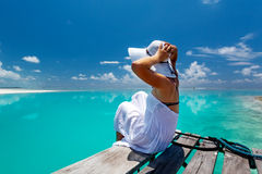 Caucasian woman takes rest. At wooden pier to Indian ocean Stock Image