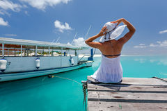 Caucasian woman takes rest at wooden pier to Indian ocean Royalty Free Stock Photography