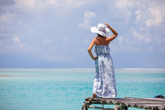 Caucasian woman takes rest at wooden pier to Indian ocean Royalty Free Stock Photos