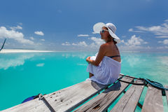 Caucasian woman takes rest at wooden pier to Indian ocean Stock Photos